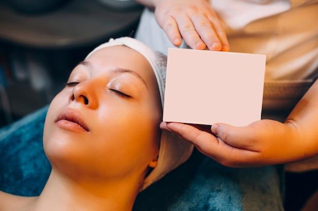 Dłonie kosmetyczki pokazujące pudełko produktu, który został nałożony na twarz kobiety opartej na łóżku spa.