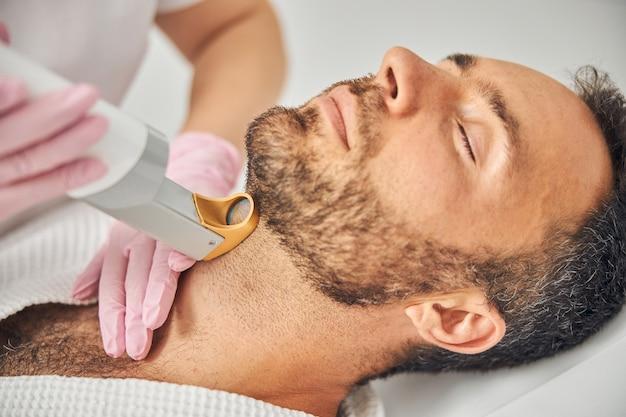 Dłonie kosmetyczki w sterylnych rękawiczkach usuwające niechciane włosy z męskiej szyi za pomocą urządzenia laserowego laser