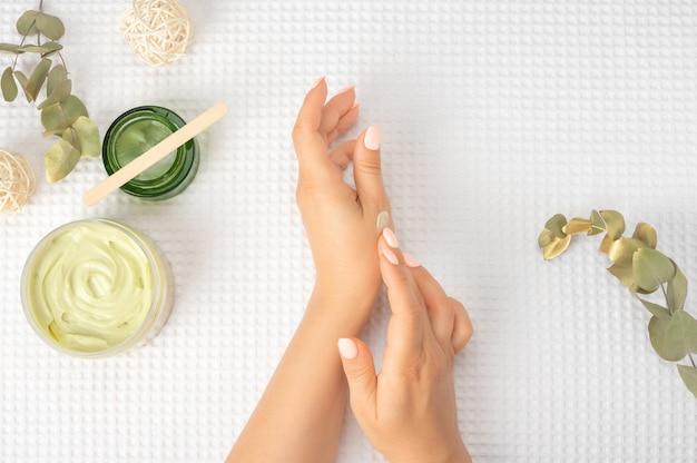 Dłonie kwiatowe kosmetyki naturalne kobiety, ręka z jasnym kontrastowym makijażem, pielęgnacja dłoni. kobieta ręce stosując krem nawilżający do jej skóry. białe tło
