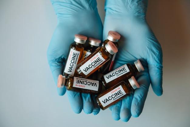 Dłonie lekarza w niebieskich rękawiczkach ostrożnie trzymają szklane fiolki z etykietą tekstową szczepionka covid-19. dłonie naukowca trzymające ampułki z lekiem na koronawirusa do wstrzykiwań, z bliska.