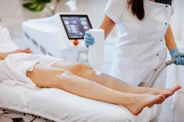 Dłonie lekarzy w niebieskich rękawiczkach medycznych trzymających płyn do depilacji i nakładających go na nogi kobiety