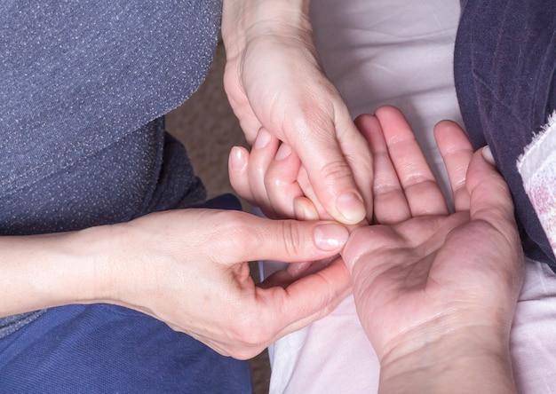 Dłonie masażysty masują palce pacjenta.