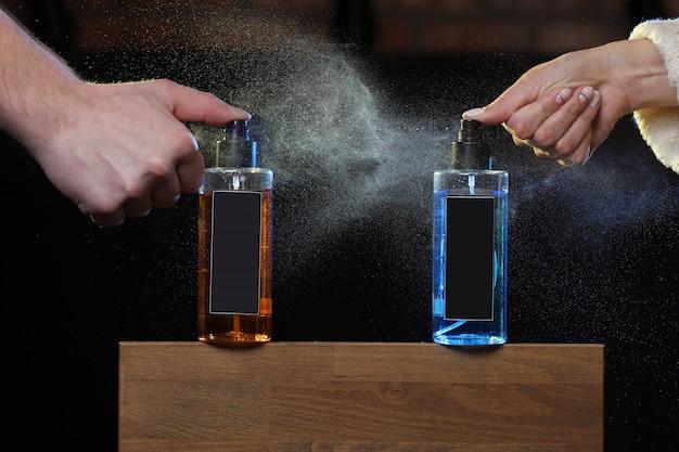 Dłonie mężczyzny i kobiety rozpylają kolorowy balsam do włosów. sprayem na czarnym tle na drewnianym stojaku.