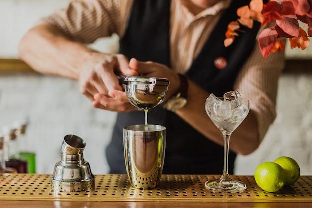 Dłonie mężczyzny wyciskające sok z limonki do wytrząsarki w barze. selektywne ustawianie ostrości, naturalne światło.
