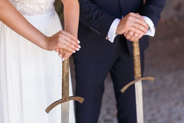Dłonie pary młodej trzymające miecze podczas ceremonii ślubnej