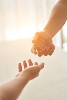 Dłonie pary wyciągnęły się do siebie przy oświetlonym słońcem pokoju