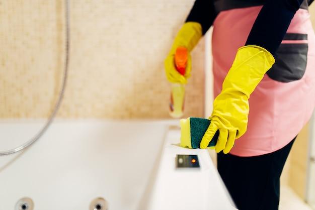 Dłonie pokojówki w gumowych rękawiczkach czyści wannę sprayem czyszczącym, wnętrze łazienki hotelowej. profesjonalne usługi sprzątania, sprzątaczki, sanitariaty