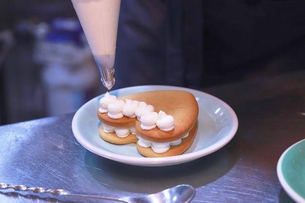 Dłonie szefa kuchni w rękawiczkach przygotowują tort na błyszczącym stole na talerzu w kuchni