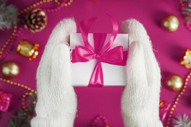 Dłonie w ciepłych białych dzianinowych rękawiczkach trzymają białe pudełko z różową kokardką na różowym stole. świąteczna kartka z życzeniami z wesołych świąt bożego narodzenia lub nowego roku.