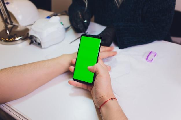 Dłonie w rękawiczkach dbają o paznokcie rąk mężczyzny. salon kosmetyczny do manicure. smartfon, zielony ekran, hromakey