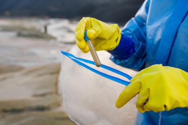 Dłonie w rękawiczkach współczesnego badacza w kombinezonie wkładającym kolbę z próbką brudnej wody do opakowania podczas badania skażonego terenu