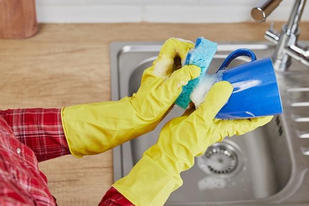 Dłonie z gąbką myją kubek pod wodą, gospodyni w żółtych gumowych rękawiczkach ochronnych myje niebieski kubek w zlewie kuchennym, czyszczenie ręczne, ręcznie, ręcznie, zmywarka do naczyń