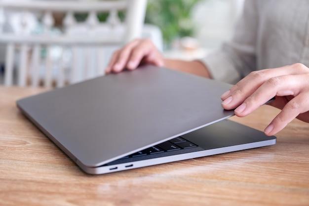 Dłonie zamykają i otwierają laptop na stole po zakończeniu korzystania z niego