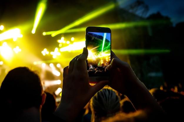 Dłonie ze smartfonem nagrywają festiwal muzyki na żywo, koncert na żywo, koncert na żywo.