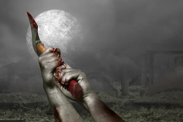 Dłonie zombie z raną trzymającą siekierę na tle sceny nocnej