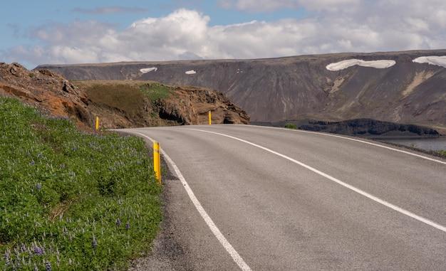 Długa asfaltowa droga otoczona wysokimi górami pod zachmurzonym niebem
