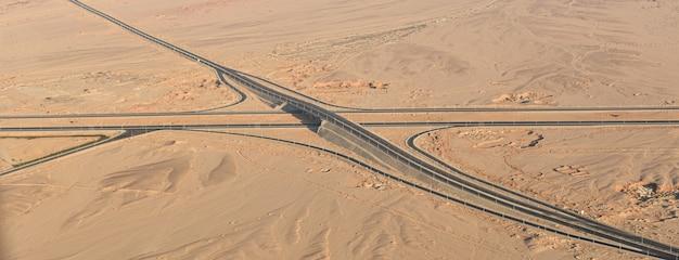 Długa autostrada na pustyni wśród gór i piasków, widok z góry