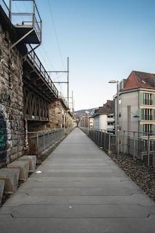 Długa, brukowana ścieżka obok łuków wiaduktu pod zachmurzonym niebem