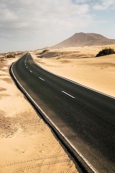 Długa czarna asfaltowa droga z pustynią i plażą