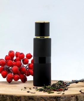 Długa czarna butelka perfum ozdobiona liśćmi żurawiny i bergamotki