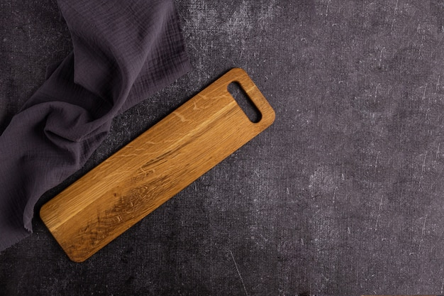Długa drewniana deska do krojenia na ciemnym tle