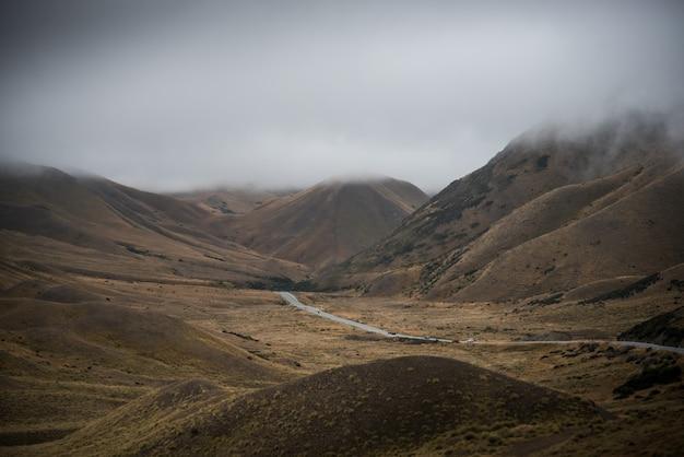 Długa droga w dolinie żółtej trawy z niebem i białą chmurą