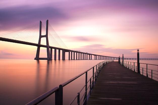 Długa ekspozycja nakręcona o świcie na moście vasco da gama. lizbona, portugalia. miejsce na tekst.