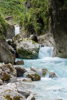 Długa ekspozycja obrazu pięknego górskiego potoku przepływającego przez skały i kamienie w dolinie.