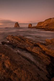 Długa ekspozycja podczas odpływu na skałach zwanych dwiema siostrami hendaye. francja, fotografia pionowa