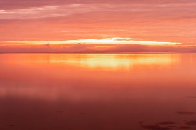 Długa ekspozycja promiennego wschodu słońca z różowożółtymi kolorami odbitymi w gładkiej powierzchni oceanu na wyspie iriomote plaży nakano