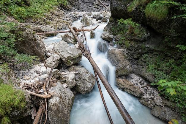 Długa ekspozycja zdjęcia pięknego górskiego potoku przepływającego przez zielone omszałe skały i kamienie.