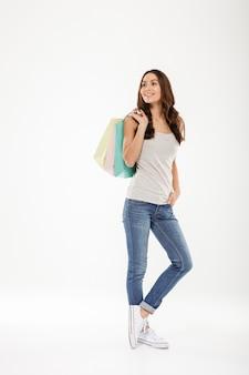 Długa galanteryjna kobieta patrzeje daleko od i trzyma kolorowych torba na zakupy, odizolowywających nad bielem