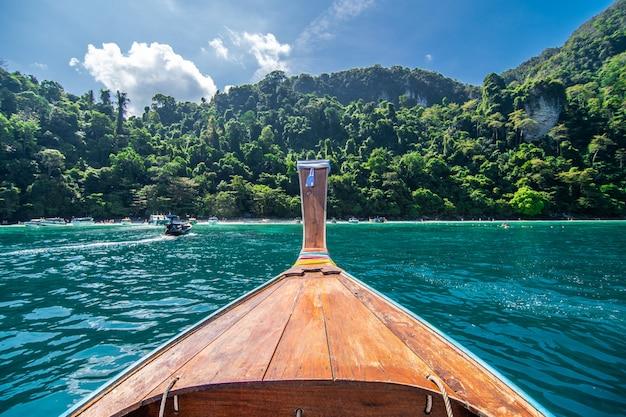 Długa łódź i błękitne wody przy majowią trzymać na dystans w phi phi wyspie, krabi tajlandia.