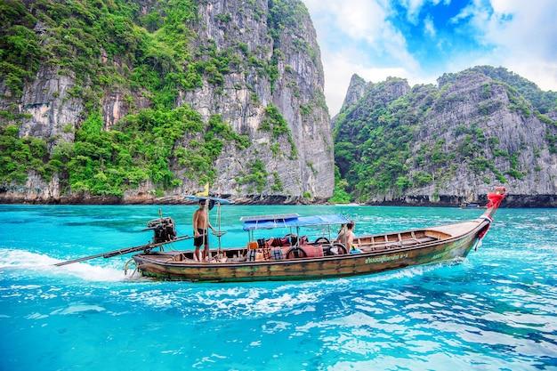 Długa łódź i turysta w zatoce maya na wyspie phi phi. zdjęcie zrobione 1 grudnia 2016 r. w krabi w tajlandii.