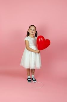 Długa, nieostrożna, obojętna dziewczyna w białej sukni trzymająca czerwony balon w kształcie serca