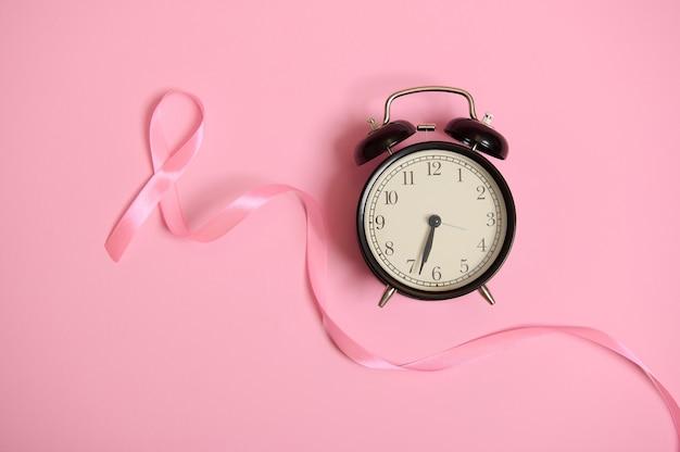 Długa różowa wstążka satynowa, której jeden koniec jest bez końca, a budzik na różowym tle. symbol świadomości raka piersi. październikowa kampania miesiąca świadomości. międzynarodowy dzień walki z rakiem, walka z rakiem piersi.