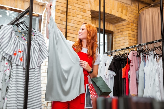Długa sukienka. wesoła podekscytowana młoda dziewczyna czuje się szczęśliwa i uśmiechnięta, trzymając wspaniałą długą sukienkę w sklepie z ubraniami