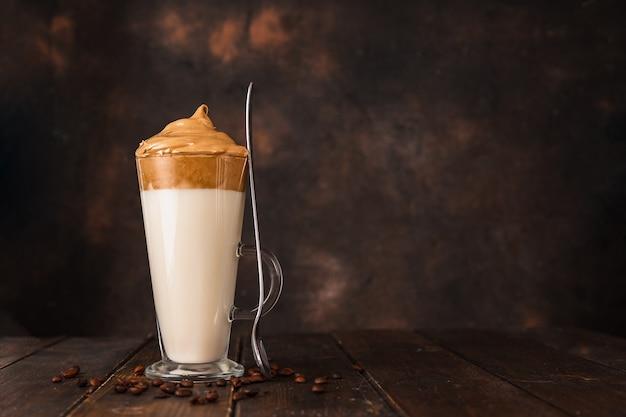 Długa szklanka z bardzo modną bitą kawą dalgona na ciemnym tle