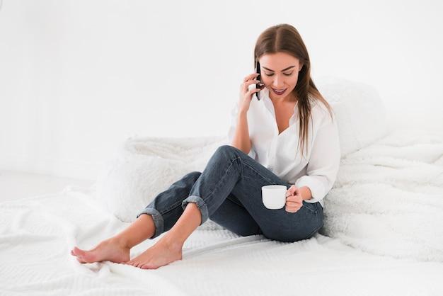 Długa widok kobieta pije kawę w łóżku