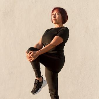 Długa widok kobieta rozciąga jej nogi