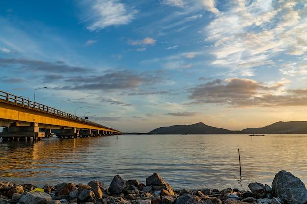 Długi betonu most krzyżuje jezioro z niebieskim niebem i górą