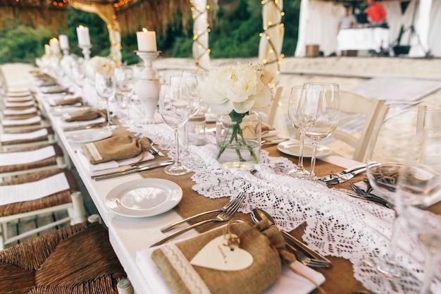 Długi biały stół stoi pod białymi namiotami na piaszczystej plaży
