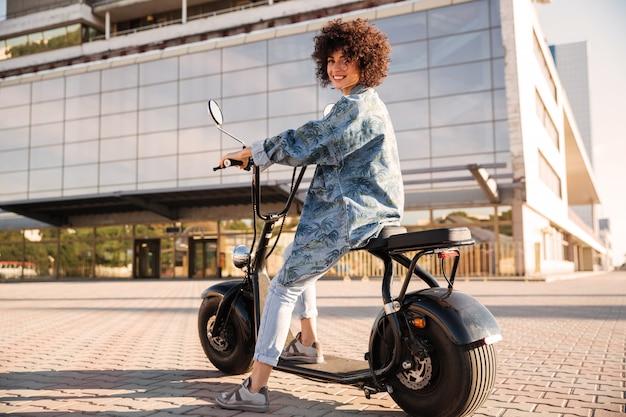 Długi boczny widok uśmiechnięty kędzierzawy kobiety obsiadanie na motocyklu