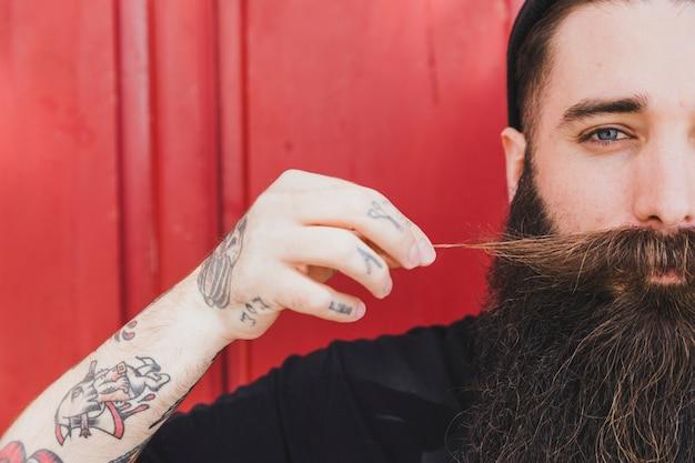 Długi brodaty młody człowiek ciągnie jego wąsy przeciw drewnianej ścianie