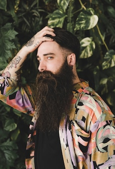Długi brodaty młody człowiek z rękami na głowie patrzeje kamerę