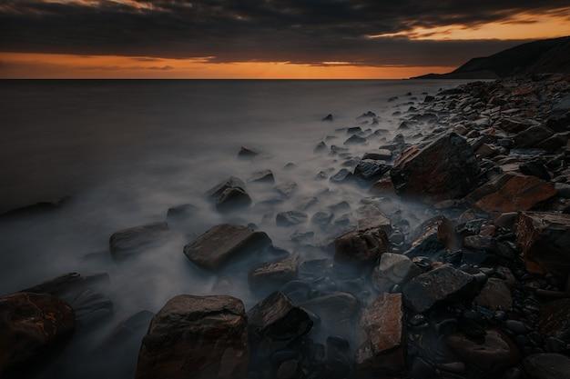Długi czas ekspozycji dramatyczny zachód słońca krajobraz ze skalistym wybrzeżem morza czarnego