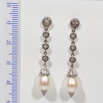 Długi designerski złoty kolczyk z perłami i diamentami na białym tle obok linijki