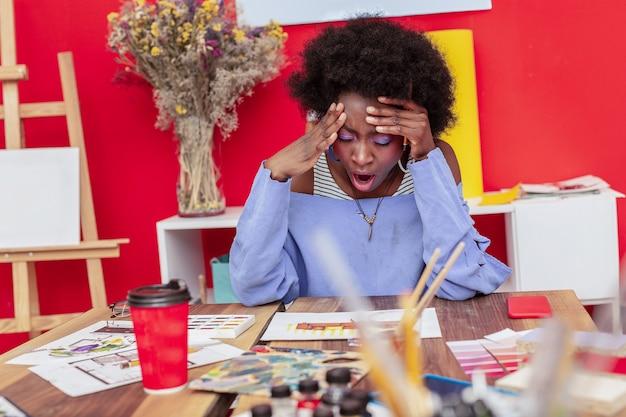Długi dzień. piękna stylowa projektantka z jasnym makijażem ziewająca po długim dniu w pracy