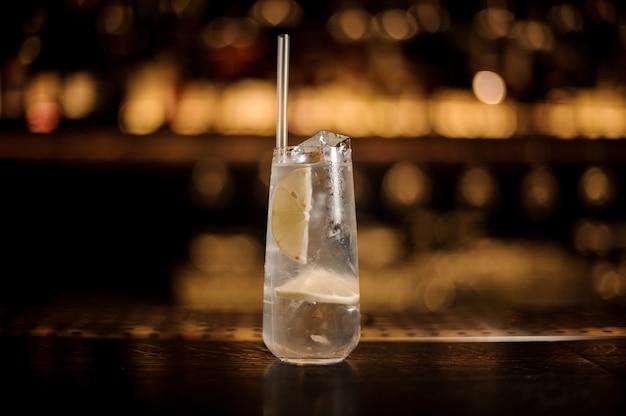 Długi kieliszek napoju wypełniony koktajlem toma collinsa na barze