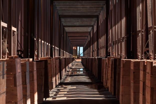 Długi korytarz w budynku przemysłowym z cieniami kolumn na ziemi